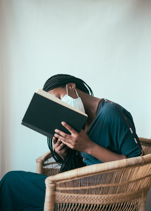 Faceless ethnic woman in protective mask reading book