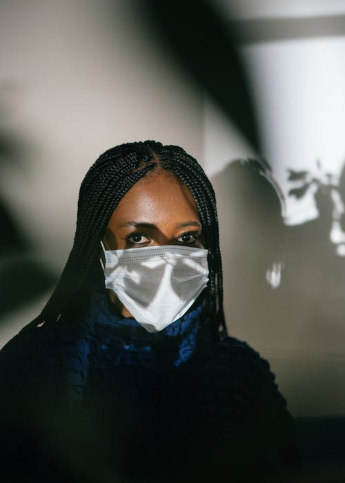 Black woman in medical mask with shadow on face