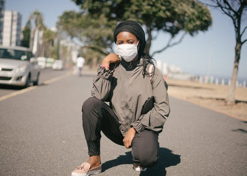 Ethnic woman squatting in protective mask on road