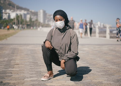 Ethnic female in outerwear and protective mask squatting on street