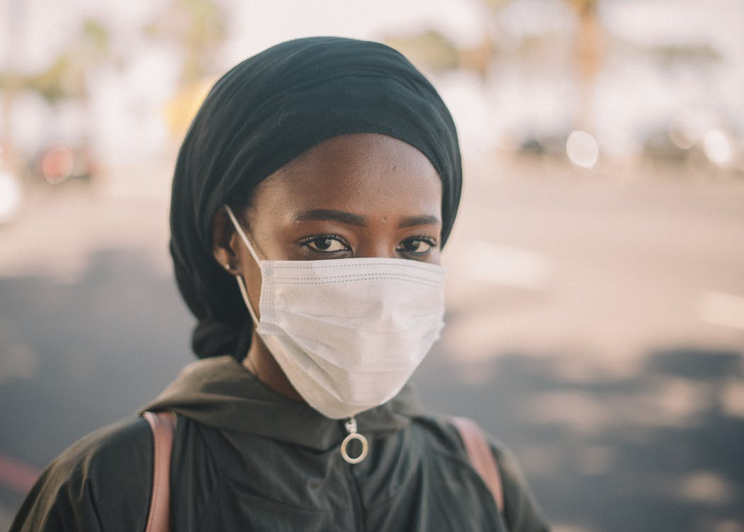 Unrecognizable young ethnic woman in jacket and headscarf and protective mask standing on city street