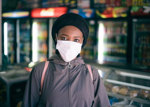 Black woman in protective mask in grocery store