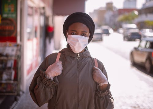 Unrecognizable black female in outerwear and headscarf and protective mask and gloves standing on sidewalk of city street