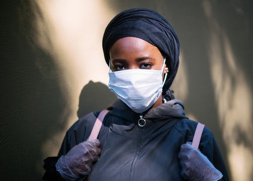 Ethnic female in protective mask and gloves against street wall