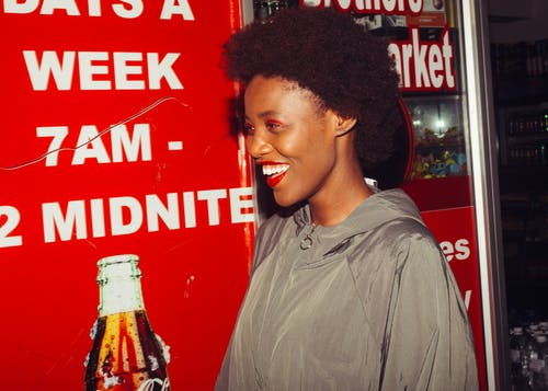Cheerful black woman near advertising in supermarket