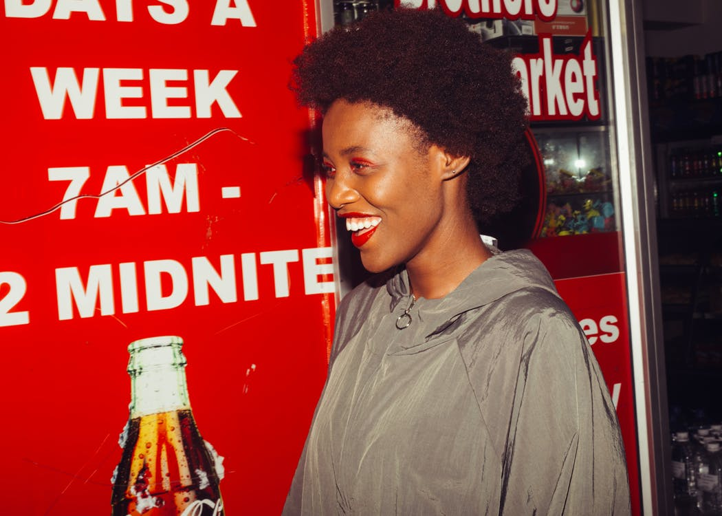 Side view of laughing African American female in outerwear standing near advertising space in supermarket looking away