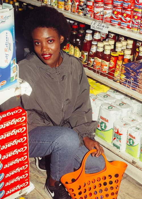 Positive black woman among shelves with groceries