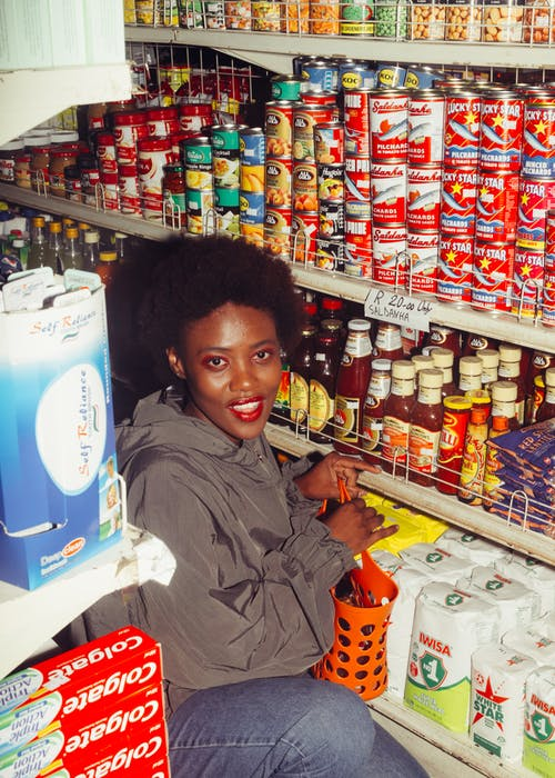 Cheerful black woman choosing products in supermarket