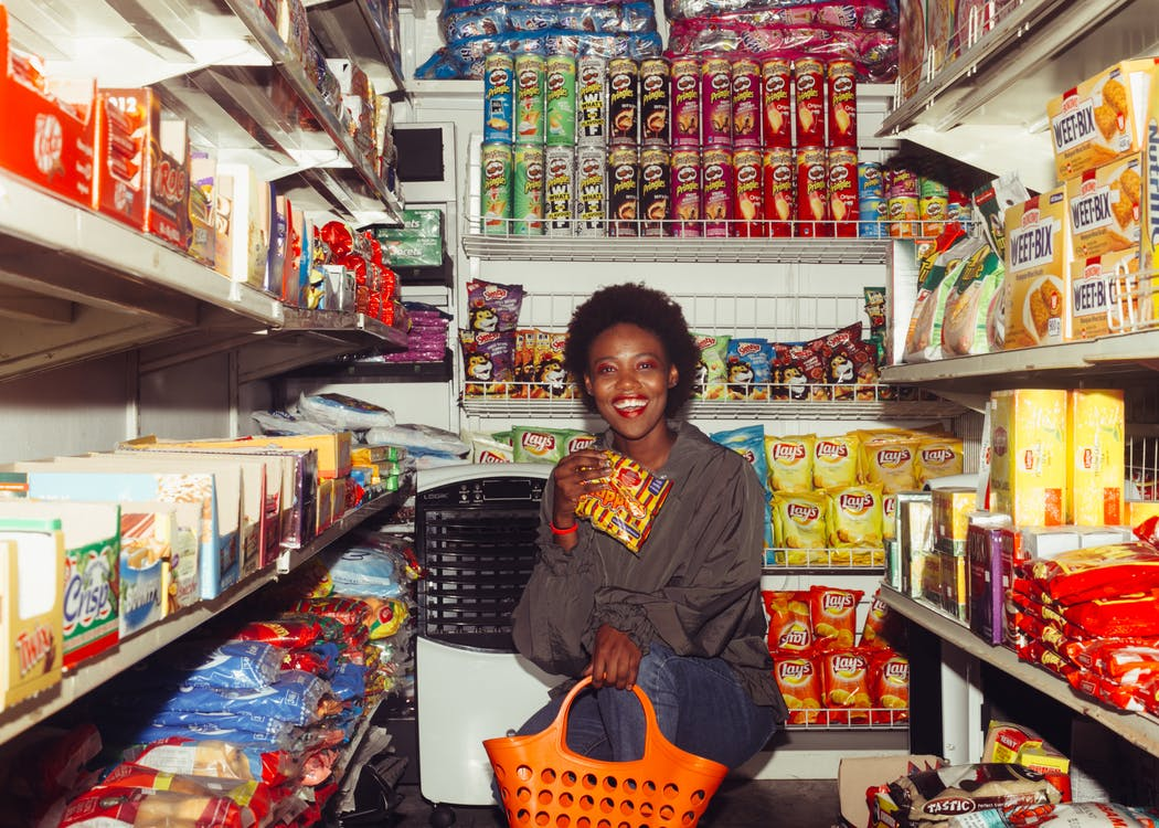 Happy black female in casual clothes with shopping bag demonstrating product squatting among grocery shelves while choosing goods in supermarket