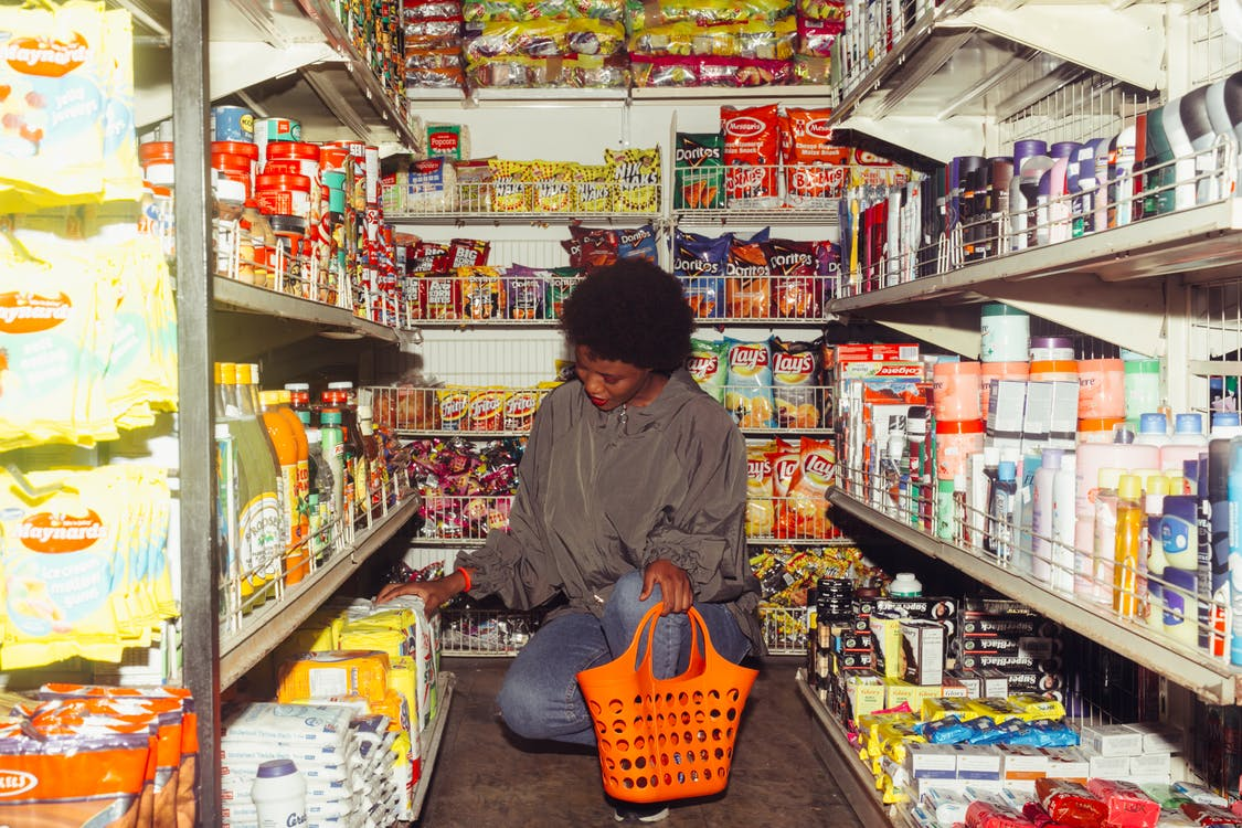 Black woman selecting products for buying in supermarket