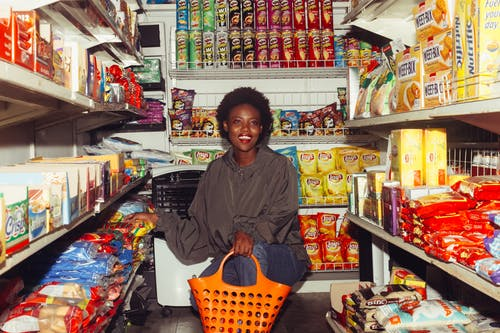 Smiling black woman choosing goods in grocery store