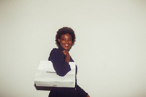 Happy black woman with paper bag on white background