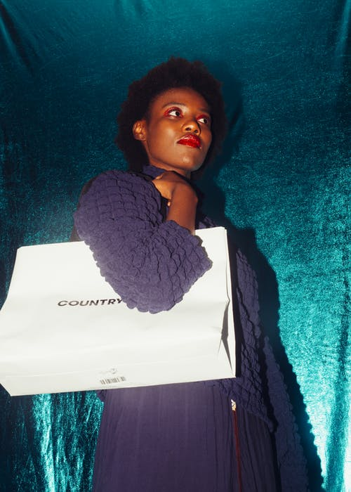Trendy black woman with shopping bag