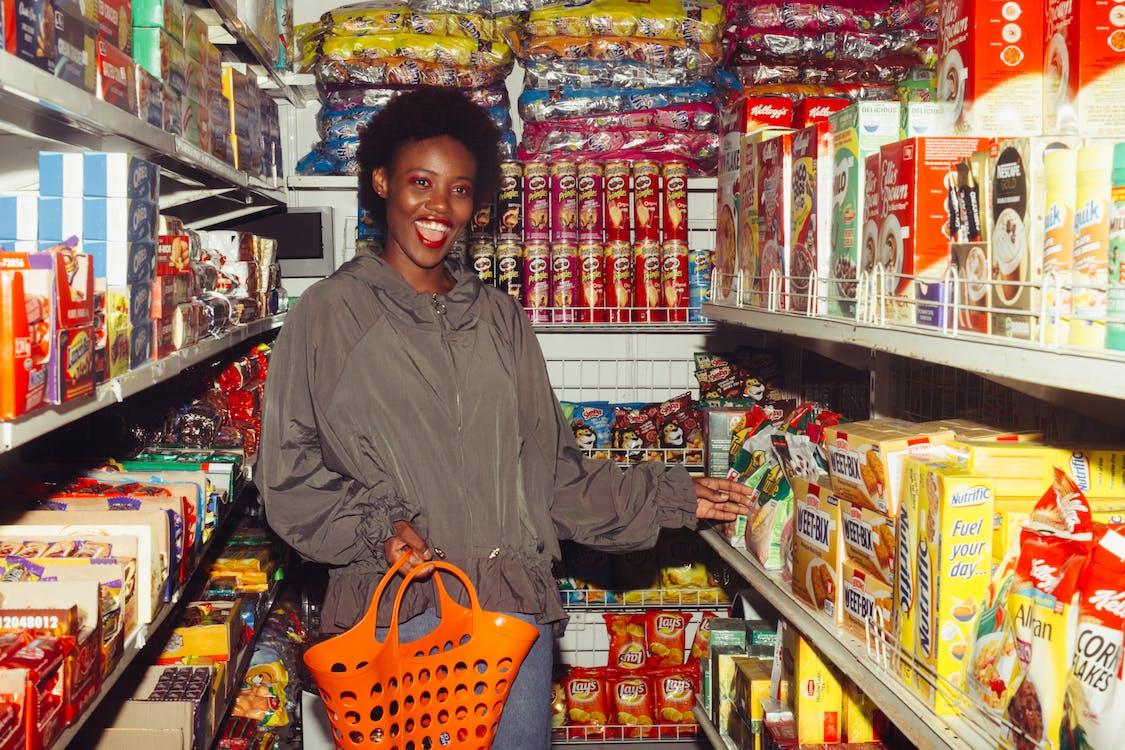 Funny black woman choosing food in grocery shop