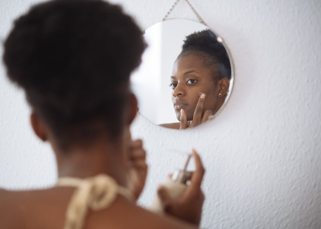 Focused woman applying cream on face in bathroom