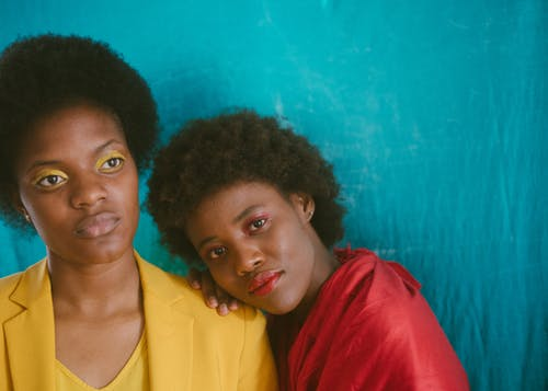 Black women standing in front of aquamarine textile background
