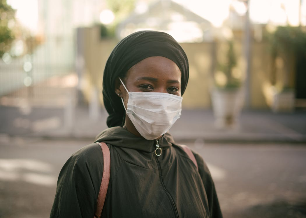 African American woman in face mask on city street