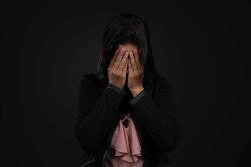 Woman in Black Cardigan Covering Her Face