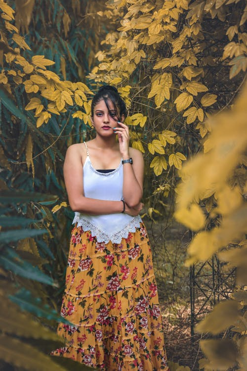Woman in White Tank Top and Yellow Floral Skirt Standing Beside Yellow Leaves