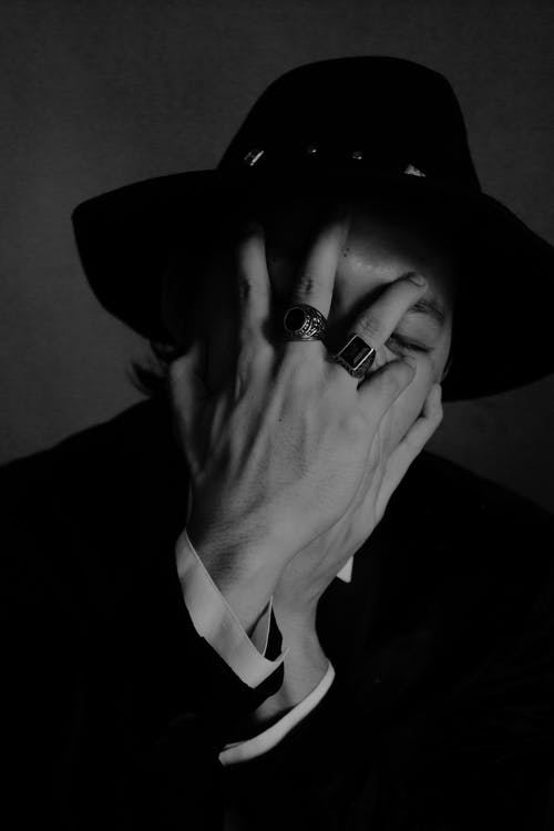 Unrecognizable elegant man with closed eyes covering face with hands