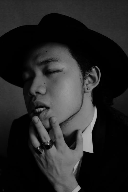 Trendy ethnic man touching lips sensually
