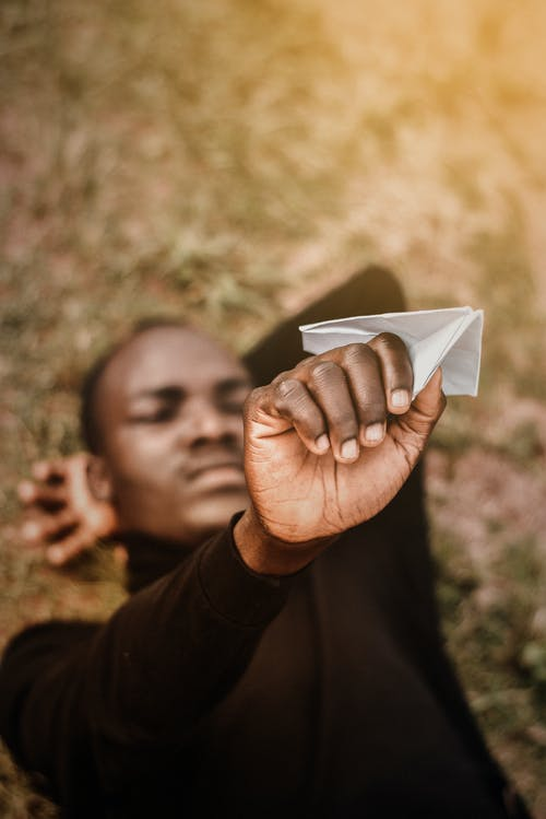 High angle soft focus of young thoughtful African American man holding paper plane with hand behind hand on dry grass