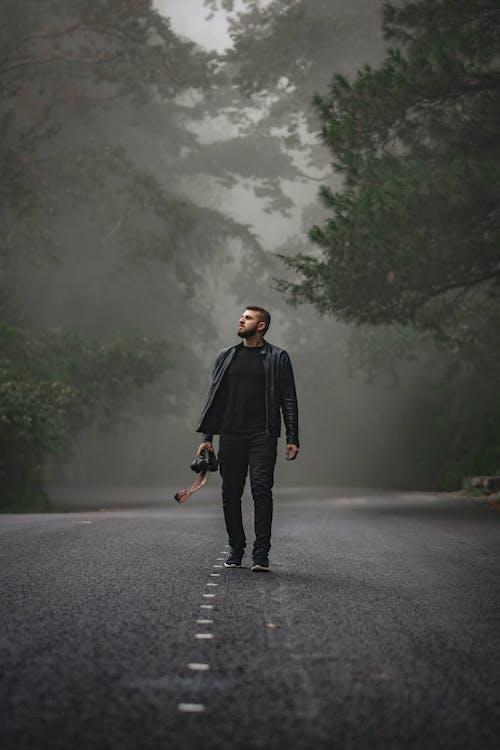 道路に立っている黒いコートの男