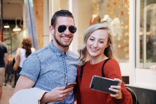 Cheerful young couple using smartphone in modern mall
