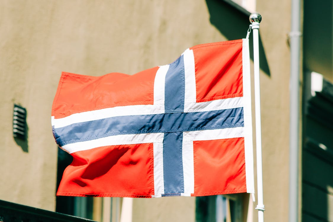 Flag of Norway with white blue and red stripes waving on flagstaff against building