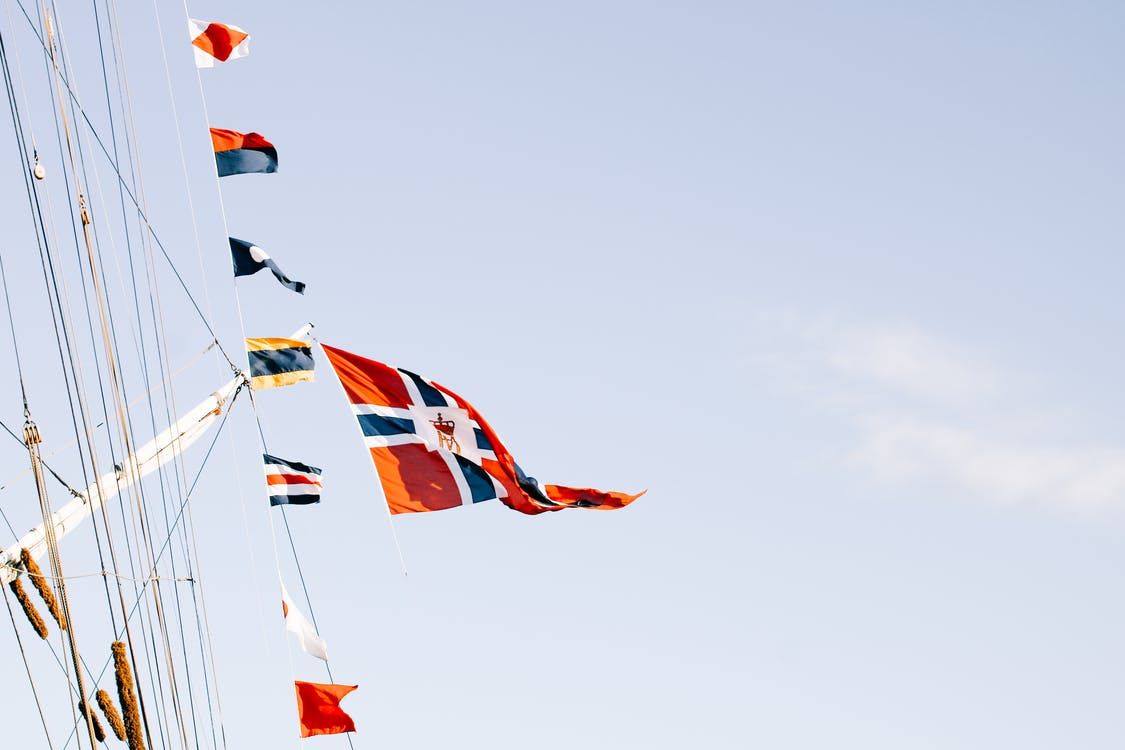 Various flags waving on rope against blue sky