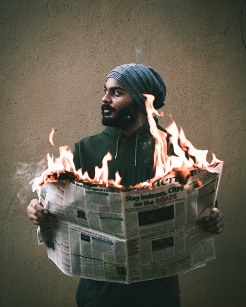 Ethnic man with burning newspaper in hands