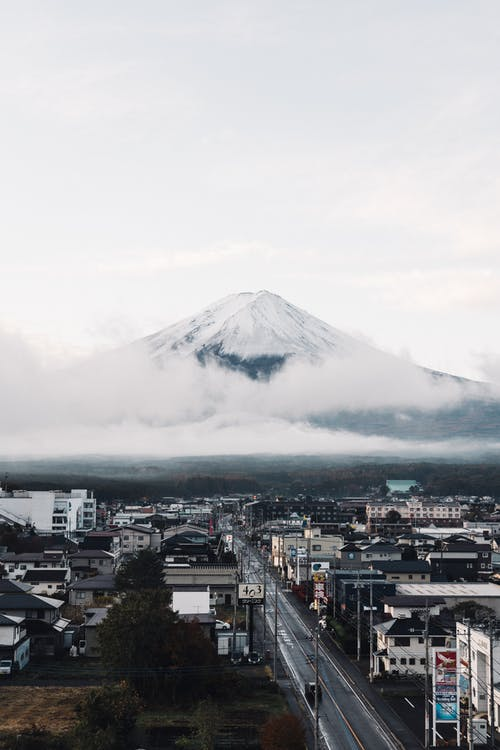 White Clouds over City With Mountain in Distance