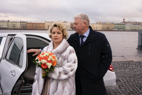 Couple of mature lovers standing near car