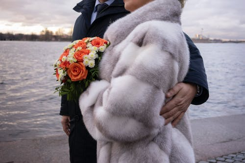 Unrecognizable male in suit hugging anonymous woman with flowers while standing on embankment near rippling water against cloudy sky in city