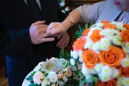 Unrecognizable groom with bouquet putting ring on finger of anonymous groom while standing near table with flowers during wedding ceremony