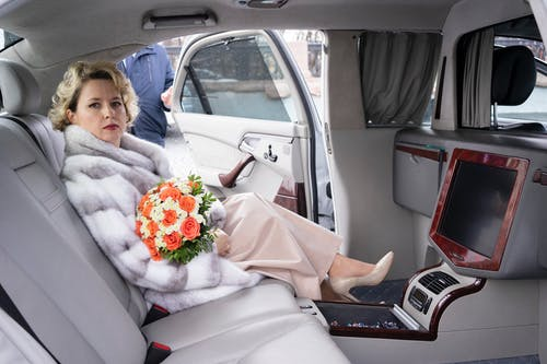 Woman in White Dress Sitting on Car Seat