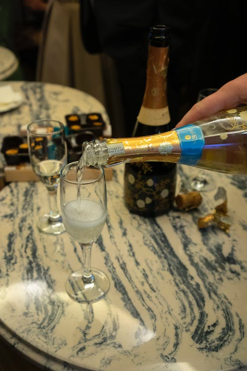 Unrecognizable person pouring alcohol drink in glass placed on marble table near bottle of champagne in luxury restaurant during celebration