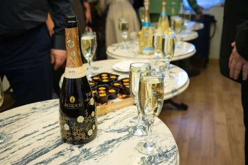 Set of bottles with alcohol drinks and wineglasses placed on tables near snacks during event celebration in company in restaurant