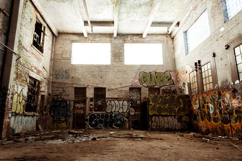 Old concrete building with graffiti walls and rough floor