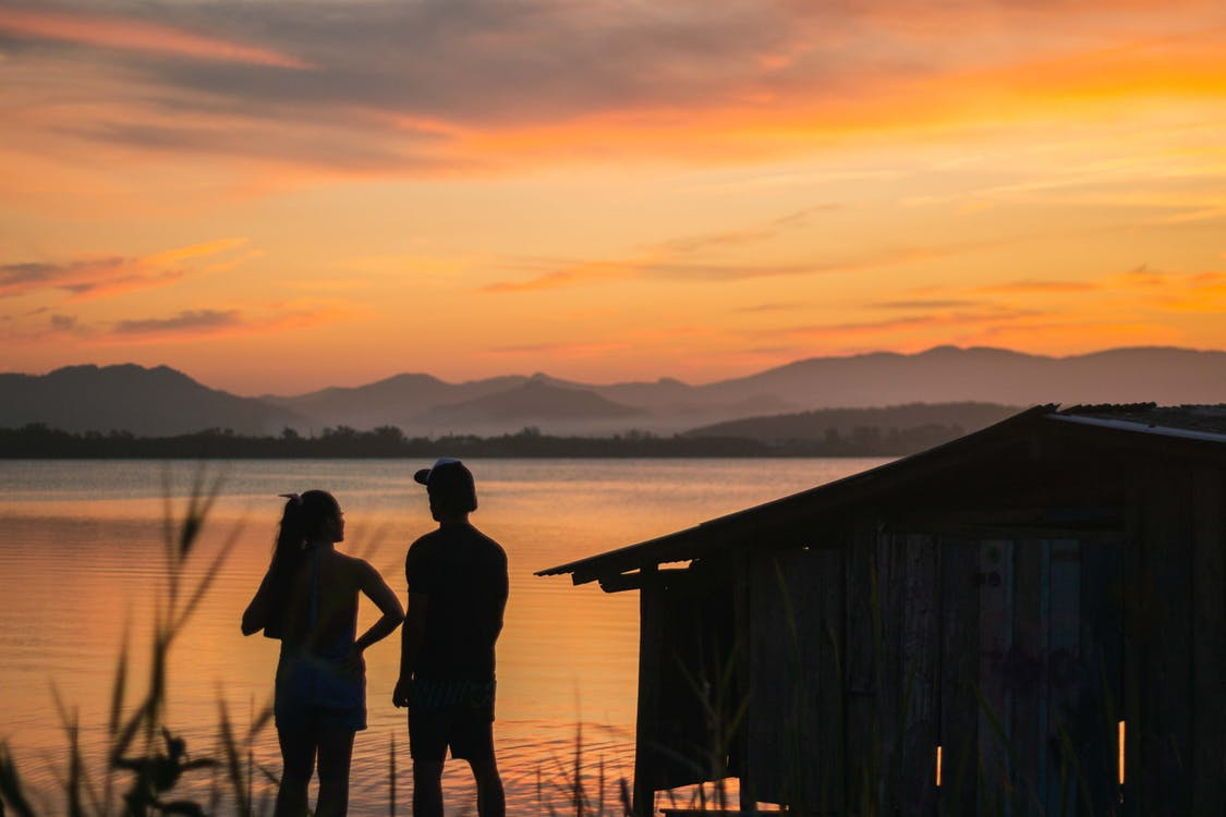 Silhouette of 2 Person Standing on Wooden Dock during Sunset
