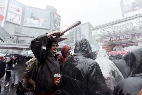 Happy man under rain in crowd
