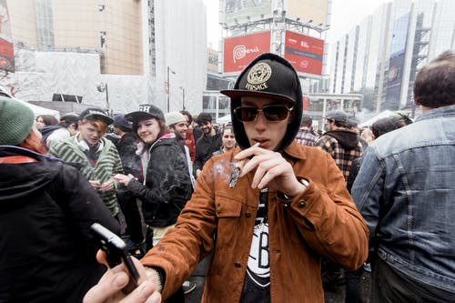 Young man in hat with hood standing on crowded street with smartphone in hand while smoking joint in city center