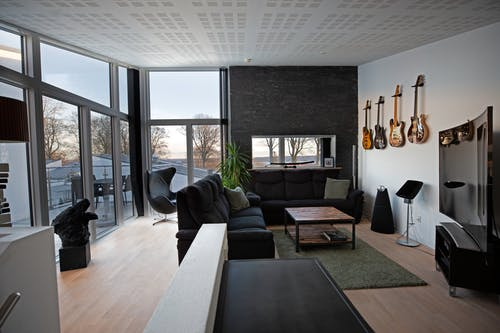 Contemporary living room with comfortable sofa and armchair near table located next to big windows against guitars on wall inside