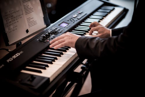 Crop man playing piano in room