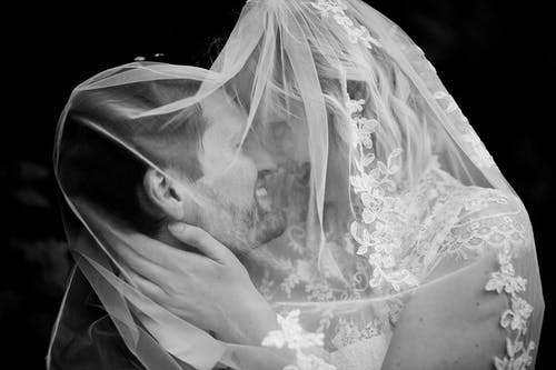 Black and white of happy bride and groom covered in veil while hugging and looking at each other on black background