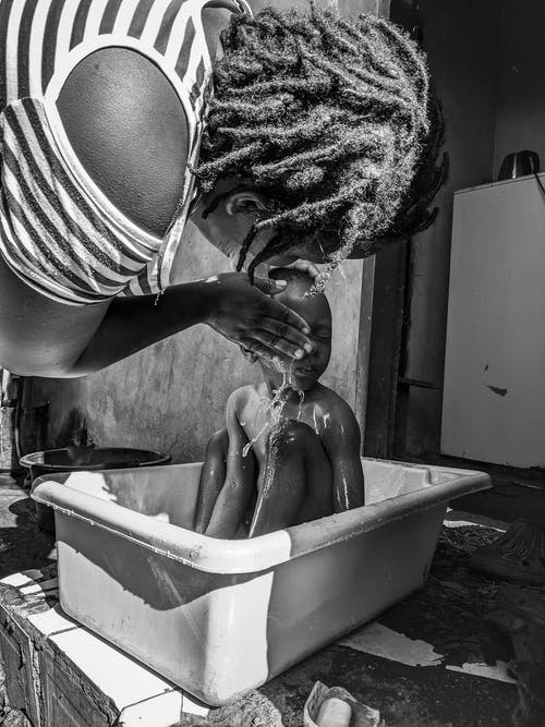 Black and white of unrecognizable African American woman washing little boy in bathtub on street during daylight in summer time