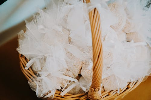 Basket with organza bags filled with risposer on wedding day