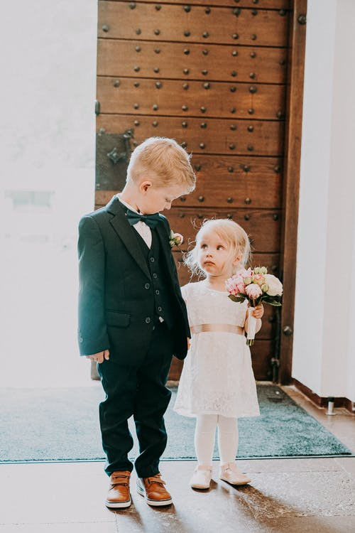 Full body of little girl in white bridal gown holding wedding bouquet and looking at boy in black elegant tuxedo in sunlight