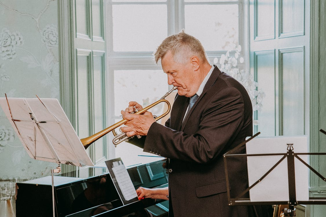 Side view of concentrated senior musician with grey hair in dark elegant suit looking at notes on sheet and playing trumpet next to pianist