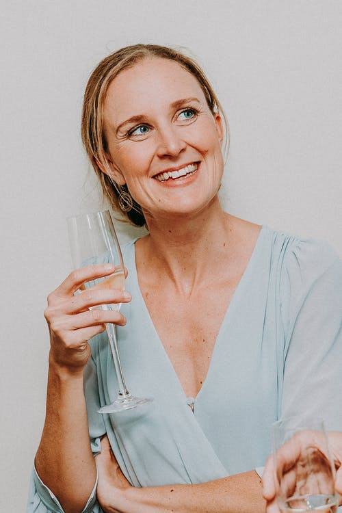 Adult woman drinking champagne with smile